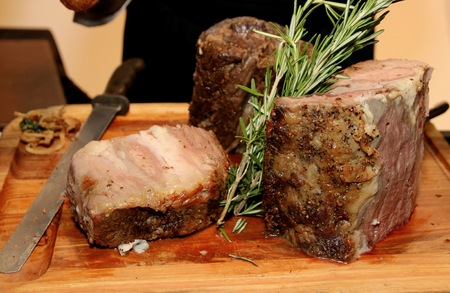 The prime rib is being sliced for the party guests. Stock Photo