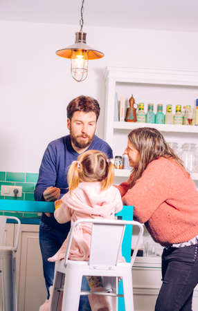 Happy family sharing good time in the modern kitchen. Dad feeding his little girl while mom is looking
