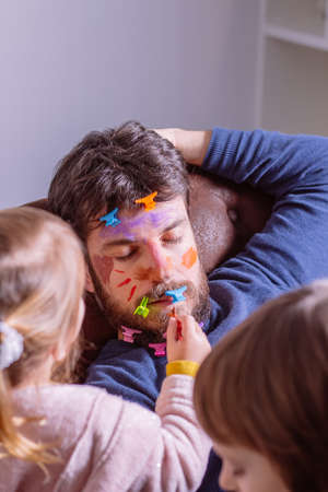 Young father sleeping on the sofa at home while children paint his face with colored watercolors