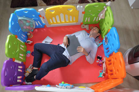 Businessman sleeping with laptop in his hands inside baby playground at home. Work from home concept