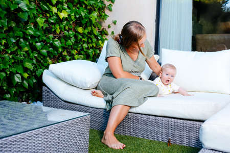 Mother and her baby girl on white sofa in the home garden. Happy family at home in summer concept