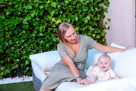 Young mother sitting next to her baby on the sofa in the home garden. Happy family in summer concept Standard-Bild