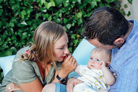 Young mother and father holding their baby daughter with love and affection. Happy family outdoors in the home garden in summer