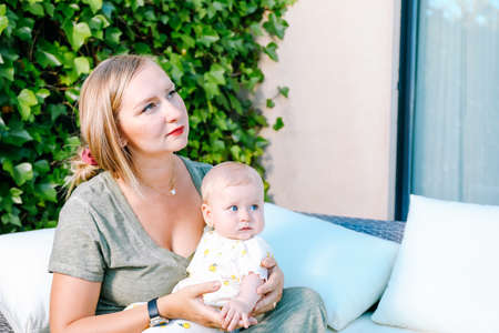 Young mother holding her baby daughter sitting in white sofa outdoors in home garden Standard-Bild