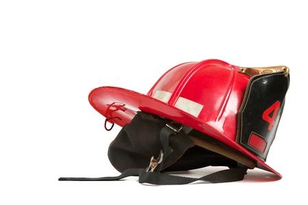 Vintage červená hasiči helma s antracitově šedé plsti klapky na uši, popruhy, černá kůže hřeben, mosazné obložení a okrasné zlaté šití. Stolní zátiší na bílém pozadí. Reklamní fotografie