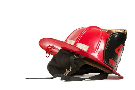 Vintage red fire fighters helmet with charcoal grey felt ear flaps, straps,black leather crest, brass trim, and ornamental gold stitching.  Table top still life on white background. Stock Photo