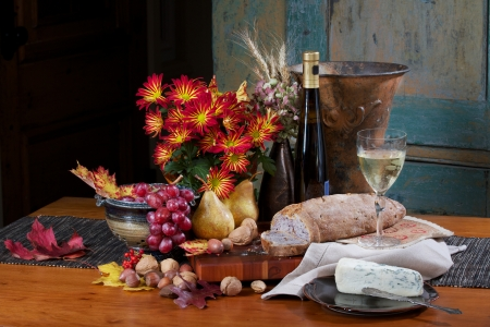 Still life on antique maple table with walnut bread, gorgonzola cheese, Bosc pears, nuts, red grapes and white wine  Flowers, pottery bowl, silver knife, and copper vase are accessories  Background is antique painted cupboard.