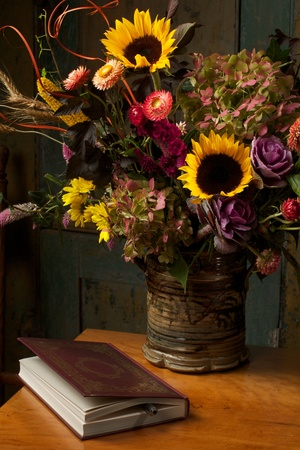 Beautiful autumn still life with flowers in a rustic handmade stoneware vase  and gold embossed leather bound book   They are grouped on an antique dropleaf table  Low key, dark background, spot lighting, and rich Old Masters color palette