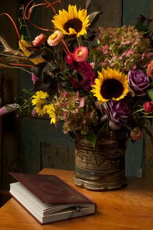 Krásné podzimní zátiší s květinami v rustikálním ruční kameninové vázy a zlaté reliéfní kožené vázané knihy jsou seskupeny na antický dropleaf tabulky low key, tmavé pozadí, bodové osvětlení, a bohaté starých mistrů paleta barev Reklamní fotografie