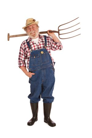 Smiling senior farmer with straw hat, plaid shirt, bib overalls, lifting hay fork over one shoulder  Vertical layout, isolated on white backgound with copy space