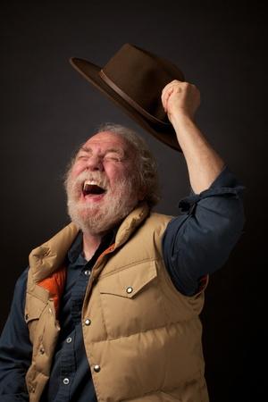 Radostné starší muž křičí a vlny svůj klobouk do vzduchu Reklamní fotografie
