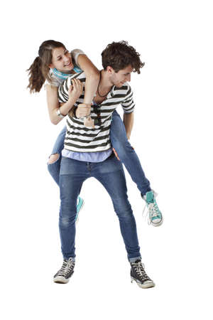 Laughing teen girl playfully jumps up on teen boys back. Both wear stripes, jeans, and sneakers. Vertical, isolated on white, copy space. Stock Photo