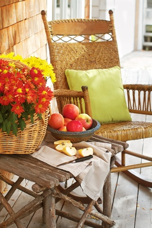 Closeup of country porch outdoors with apple still life on rustic table and antique rocking chair  Cedar shingles in background and a vertical format