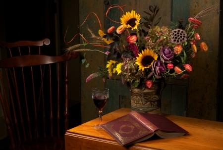 Autumn still life with flowers in handmade stoneware vase, goblet of red wine, and gold embossed leather bound book on antique wooden drop leaf table and Windsor chair. Low key, dark background, copy space.