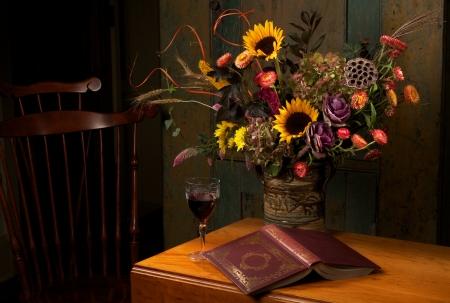 Podzimní zátiší s květinami na ruční kameniny vázy, sklenice červeného vína, a zlaté reliéfní kožené knihy vázané na starožitné dřevěné pokles listí stůl a židle Windsor. Low key, tmavé pozadí, copy space.