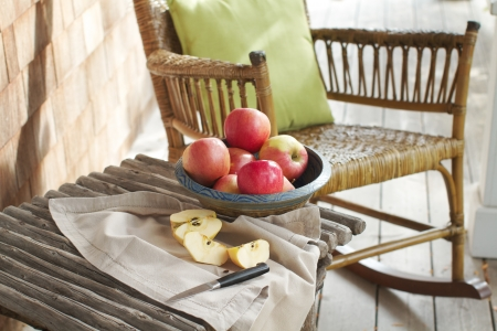 Closeup of country porch outdoors with apple still life on rustic table and antique rocking chair. Cedar shingles in background. Horizontal format and copy space. photo