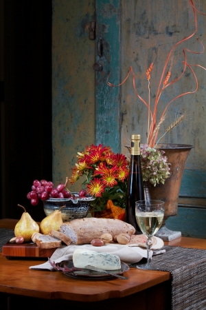 Still life on antique maple table with walnut bread, gorgonzola cheese, Bosc pears, nuts, red grapes and white wine. Flowers, pottery bowl, silver knife, and copper vase are accessories. Background is antique painted cupboard. Vertical format with copy sp Stock Photo