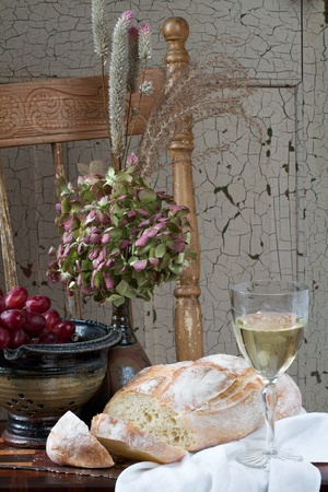 life loaf: French country still life with crusty loaf of bread, white wine, flowers and red grapes. Background is rustic chair and painted door. Vertical format and copy space.