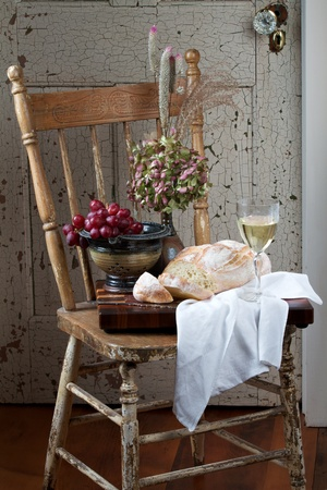French country style still life with crusty loaf of bread, white wine, flowers and red grapes. Background is rustic chair and painted door. Vertical format and copy space.