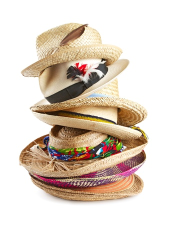 Vertical stack of eight straw hats in a variety of shapes, textures, colors, and sizes, trimmed with ribbons, feathers, and raffia. Isolated on white background, vertical format.