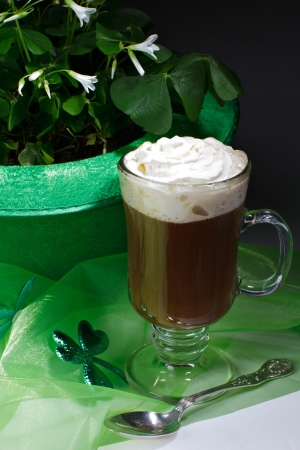 Glass of Irish coffee topped with whipped cream and cinnamon, next to green bowler hat filled with shamrocks. Sheer green fabric and silver teaspoon in foreground, dark background. Vertical layout and copy space.
