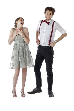 Happy teen couple wearing formal occasion clothes stand together and laugh  Vertical, isolated on white, copy space  photo