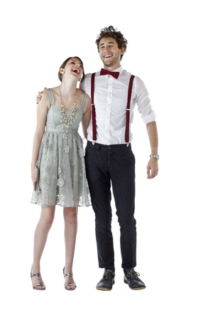 Teen girl and boy dressed formally for a prom hug each other and laugh  Vertical, isolated on white, copy space