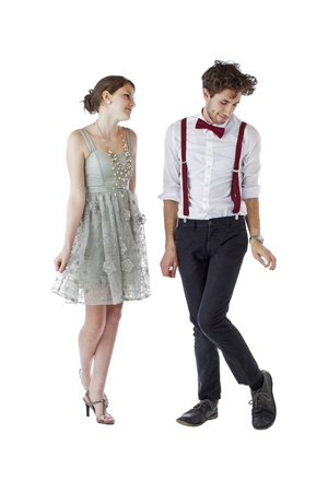 Shy teen girl and boy dressed formally for a prom bow slightly to each other  Vertical, isolated on white, copy space   photo
