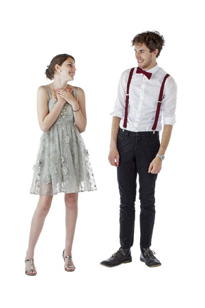 Teen girl and boy dressed formally for a prom look at each other with pleased expressions  Vertical, isolated on white, copy space
