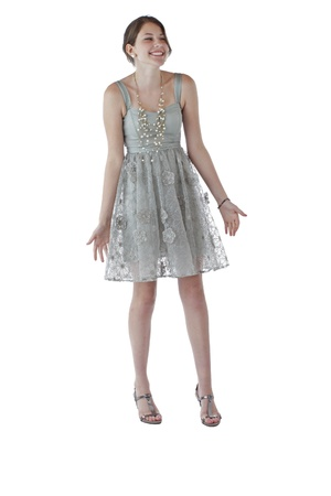 Beautiful young teenage girl with long brown hair dances in lacy silver party dress  Vertical, isolated on white with copy space  photo