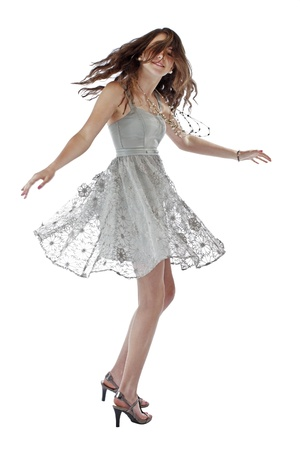 Beautiful young teenage girl with long brown hair dances in lacy silver party dress  Vertical, isolated on white with copy space