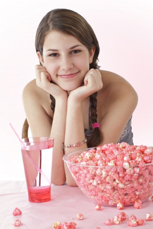 braid: Smiling teen girl with long brown braids leans elbows on table and chin on hands  Large bowl of pink popcorn and tall glass with straw are on table in foreground  Vertical, high key lighting with copy space