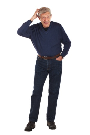 Senior man looks aside, scratching his head, with other hand in pocket  Standing full figure faces forward, wearing dark blue jeans and v-necked longsleeved shirt  Vertical format isolated on white  photo