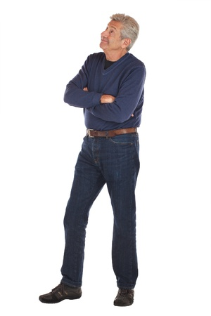 Smiling, friendly senior man in 3 4 full length pose, standing with arms crossed, looking up with eyebrows raised  He wears dark blue jeans and v-necked long sleeved shirt  Vertical format isolated on white
