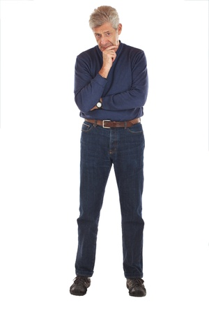 Senior man stands, arms crossed, with one hand on chin in thoughtful full length pose  He faces forward, wearing dark blue jeans and v-necked longsleeved shirt  Vertical format isolated on white