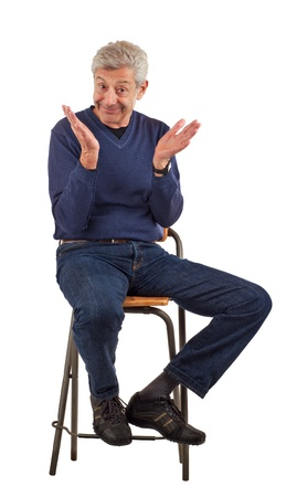 Happy senior man smiles, looks up, and raises his hands as if to clap  Wearing dark blue jeans and a longsleeved shirt, he sits on a stool  Isolated on white, vertical format  Stock Photo