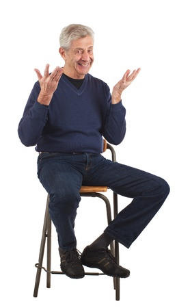 stool: Happy senior man smiles, looks up, and shrugs cheerfully  Isolated on white, vertical format  Stock Photo