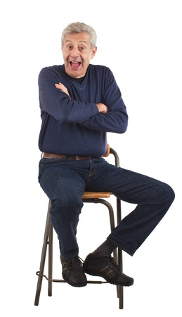 Happy senior man laughs with arms crossed while sitting on stool   He wears dark blue jeans and v-necked longsleeved shirt  Vertical format isolated on white  Stock Photo