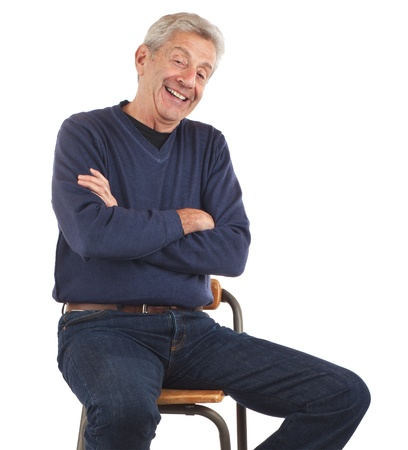 stool: Happy senior man laughs with arms crossed while sitting on stool and leaning back   He wears dark blue jeans and v-necked longsleeved shirt  Vertical format isolated on white