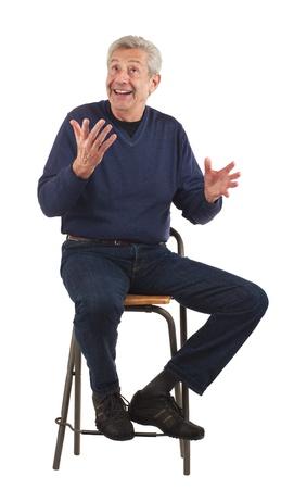 Happy senior man glimlacht, kijkt op, en haalt vrolijk Geà ¯ soleerd op wit, verticaal formaat Stockfoto