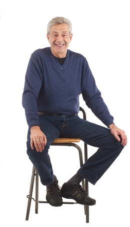 Happy senior man smiles, seated with hands on knees  Dark blue jeans and long sleeved shirt  Isolated on white, vertical format