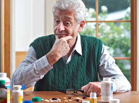 Senior man with glasses on table strokes chin and looks thoughtfully at many pills on table in front of him  Focus on man  Frontal view, green and white color palatte