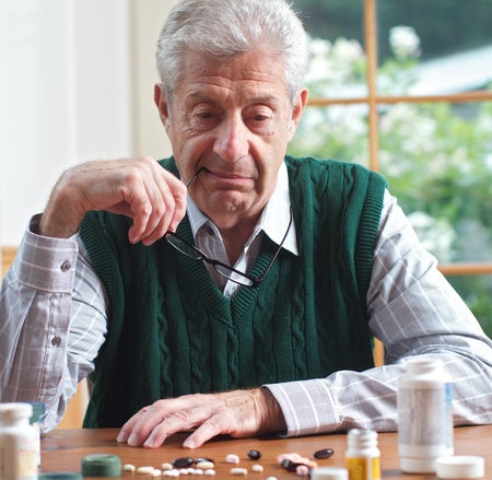 Senior man with glasses in hand looks thoughtfully at many pills on table in front of him  Focus on man  Frontal view, square format, green and white color palatte
