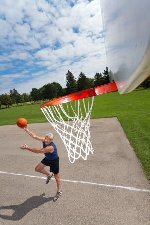 Grinning active man in his 60s enjoys shooting hoops on a basketball court outdoors  Background is green grass, trees, and blue sky with fluffy white clouds  Dynamic shadow cast on the court  Tilted wide angle shot, looking down from the net  photo