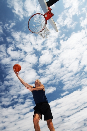 Low angle view of active man in his 60s having fun shooting hoops through an outdoor basketball net, with bright blue sky and fluffy white clouds behind him Tilted wide angle photo