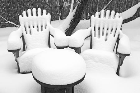 Hluboká načechraný sníh pokrývá venkovní zahradní stůl a dvě židle v rustikálním stylu