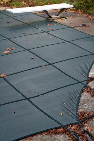 Winterized 裏庭スイミング プール プールをカバー前景縦組版、コピー領域の焦点とバック グラウンドで伸ばされたピンと張ったダイビング ボード