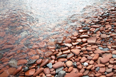 tumbled: Lake shoreline detail of rounded tumbled pebbles and broken bricks, wet from gentle lapping waves  Stock Photo