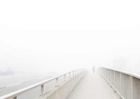 Solitary man in distance walks away, disappearing into the fog. Pedestrian walkway on bridge recedes in perspective toward subject at vanishing point. High key, desaturated, horizontal with copy space.