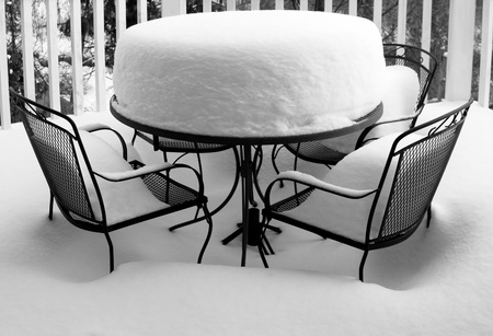 garden furniture: Garden in winter with wrought iron table and chairs covered in deep snow. Monochrome image and horizontal format.